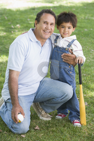Grandfather and grandson holding baseball bat and smiling stock photo,  by Monkey Business Images