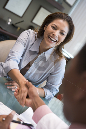 Woman shaking doctor's hand at IVF clinic stock photo, Woman sitting at desk shaking doctor's hand at IVF clinic by Monkey Business Images