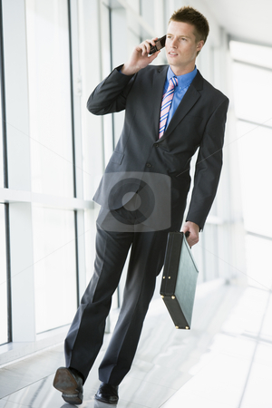 Businessman walking in corridor using cellular phone stock photo,  by Monkey Business Images
