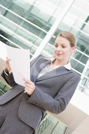 Businesswoman standing outdoors reading paperwork stock photo,  by Monkey Business Images
