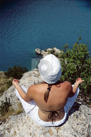 Young woman meditating on rocks at water's edge stock photo,  by Monkey Business Images