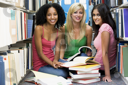 Three students working in university library stock photo, Three female students sitting on floor of library surrounded by books by Monkey Business Images