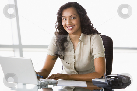 Businesswoman working at desk stock photo, Businesswoman working at desk in office by Monkey Business Images