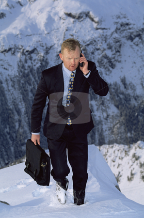 Businessman outdoors on snowy mountain using cellular phone stock photo,  by Monkey Business Images