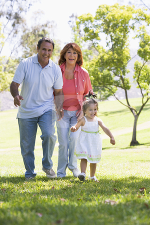 Grandparents walking in park with granddaughter stock photo,  by Monkey Business Images