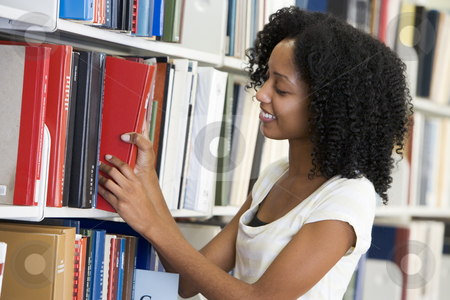 University student working in library stock photo, Female university student selecting library book from shelf by Monkey Business Images