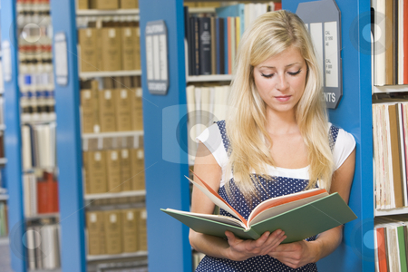 University student working in library stock photo, University student reading book in library by Monkey Business Images