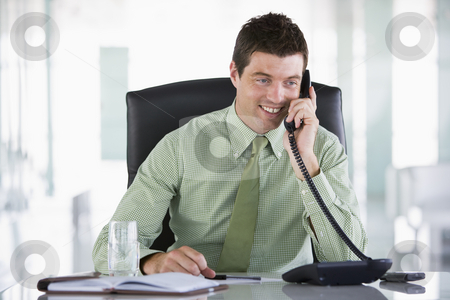 Businessman sitting in office with personal organizer on telepho stock photo,  by Monkey Business Images