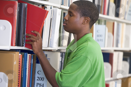 University student slecting book from library shelf stock photo, Male student selecting book from library shelf by Monkey Business Images