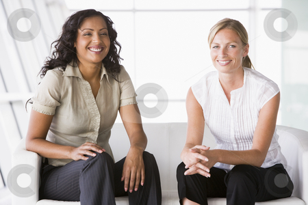 Businesswomen sitting in lobby stock photo, Businesswomen sitting in office lobby by Monkey Business Images