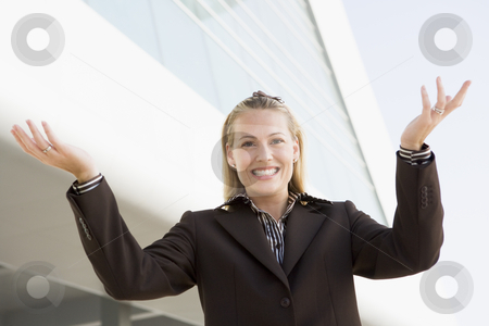 Businesswoman standing outdoors by building smiling with hands o stock photo,  by Monkey Business Images