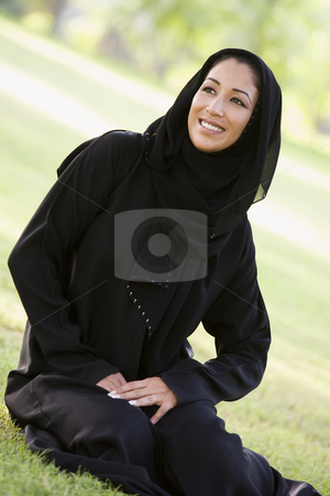 A Middle Eastern woman sitting in a park stock photo,  by Monkey Business Images