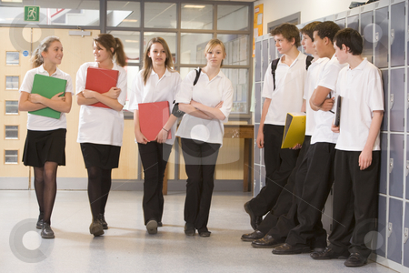 Teenage boys watching girls walk down a school corridor stock photo,  by Monkey Business Images