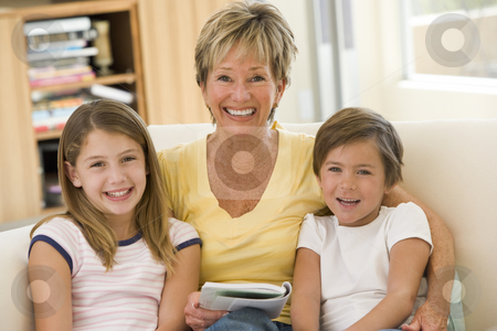 Grandmother reading with grandchildren stock photo,  by Monkey Business Images