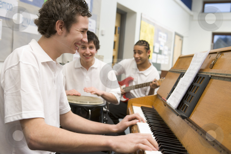 Schoolboys playing musical instruments in music class stock photo,  by Monkey Business Images