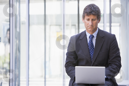 Businessman sitting in office lobby using laptop stock photo,  by Monkey Business Images