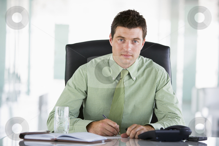 Businessman sitting in office with personal organizer stock photo,  by Monkey Business Images