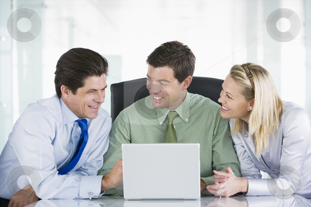 Three businesspeople in a boardroom looking at laptop smiling stock photo,  by Monkey Business Images