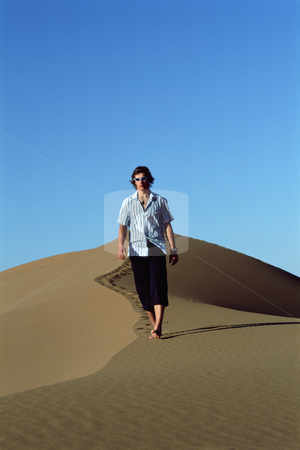 Young man walking along sand dune stock photo,  by Monkey Business Images