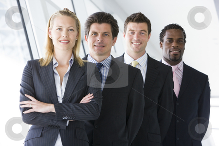 Four businesspeople standing in corridor smiling stock photo,  by Monkey Business Images