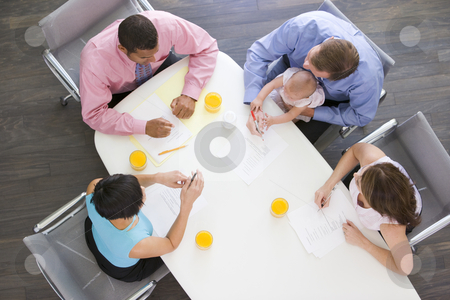 Four businesspeople in boardroom with one holding a baby stock photo,  by Monkey Business Images
