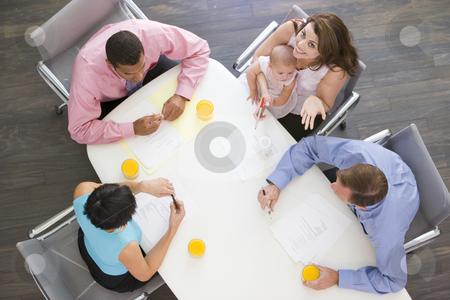 Four businesspeople in boardroom with one holding a baby smiling stock photo,  by Monkey Business Images