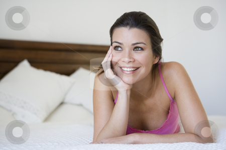 A Middle Eastern woman lying on a bed stock photo,  by Monkey Business Images