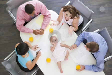 Four businesspeople in boardroom with a baby lying on the table stock photo,  by Monkey Business Images