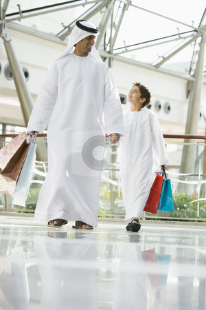 A Middle Eastern man and his son in a shopping mall stock photo,  by Monkey Business Images