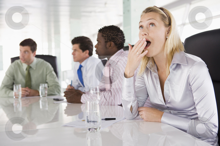 Four businesspeople in boardroom with one businesswoman yawning stock photo,  by Monkey Business Images