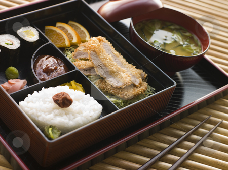 Tonkatsu Box and Miso Soup with Pickles and Sushi on a tray stock photo, Selection of Sushi items and bowl of miso soup on a tray with chopsticks. by Monkey Business Images