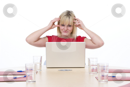 Businesswoman sitting in boardroom with laptop looking frustrate stock photo,  by Monkey Business Images