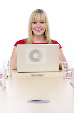 Businesswoman sitting in boardroom with laptop smiling stock photo,  by Monkey Business Images