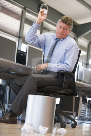 Businessman in office space throwing garbage in bin stock photo,  by Monkey Business Images