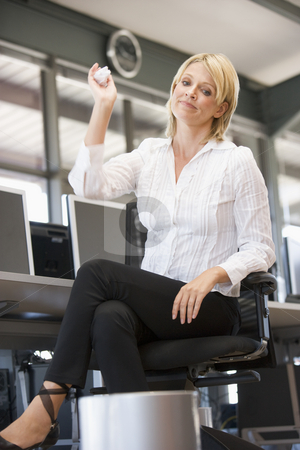 Businesswoman in office space throwing garbage in bin stock photo,  by Monkey Business Images