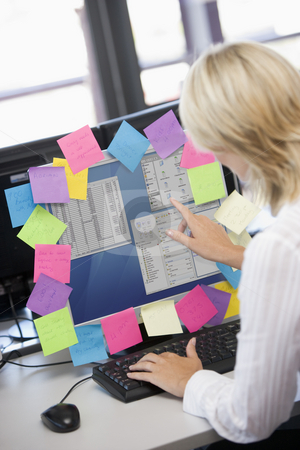 Businesswoman in office pointing at monitor with notes on it stock photo,  by Monkey Business Images