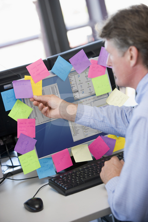 Businessman in office at monitor with notes on it stock photo,  by Monkey Business Images