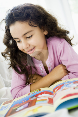 A Middle Eastern girl reading a book stock photo,  by Monkey Business Images