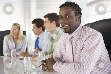 Four businesspeople in a boardroom smiling stock photo,  by Monkey Business Images