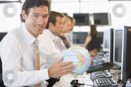 Businessman in office space with a desk globe stock photo,  by Monkey Business Images