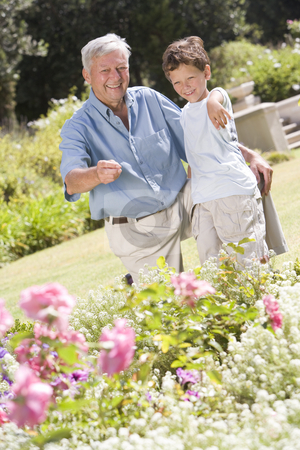 Grandfather and grandson outdoors in garden pointing at plants a stock photo,  by Monkey Business Images