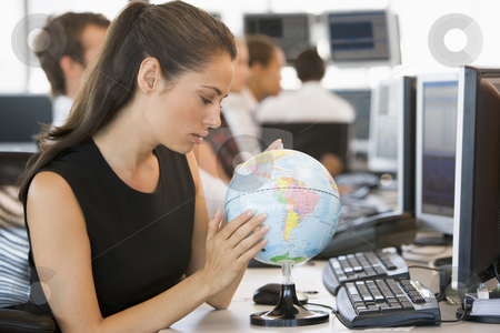 Businesswoman in office space with desk globe stock photo,  by Monkey Business Images