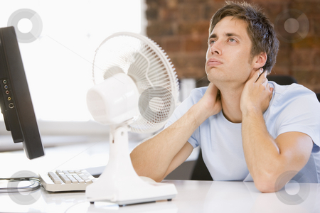 Businessman in office with computer and fan cooling off stock photo,  by Monkey Business Images