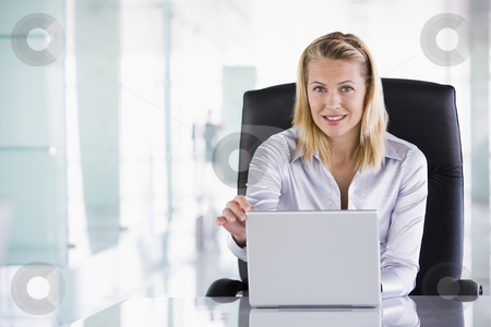 Businesswoman sitting in office with laptop smiling stock photo,  by Monkey Business Images