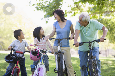 Grandparents bike riding with grandchildren stock photo,  by Monkey Business Images