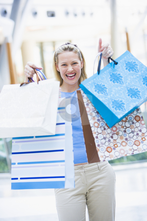 Woman shopping in mall stock photo, Woman shopping in mall holding bags by Monkey Business Images