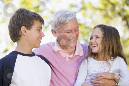 Grandfather laughing with grandchildren stock photo,  by Monkey Business Images
