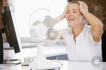 Businesswoman in office with computer and fan cooling off stock photo,  by Monkey Business Images