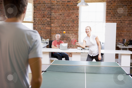 Man and woman in office space playing ping pong stock photo,  by Monkey Business Images