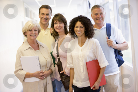 A group of adult students with backpacks standing in a campus co stock photo,  by Monkey Business Images
